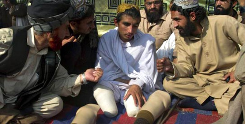 Tribesmen sit with Sadaullah Khan (C), a man from North Waziristan, who says he lost both legs and one eye in a drone strike on his house in 2009, as they demonstrate near the parliament house in Islamabad on December 9, 2010. — Reuters
