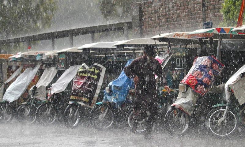 A Pakistani man runs for cover from heavy rain in Rawalpindi, Pakistan, Monday, April 27, 2015. —AP
