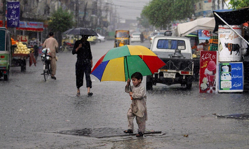 A boy holds an umbrella as he crosses a road in heavy rain, in Rawalpindi, Pakistan, Monday, April 27, 2015. —AP