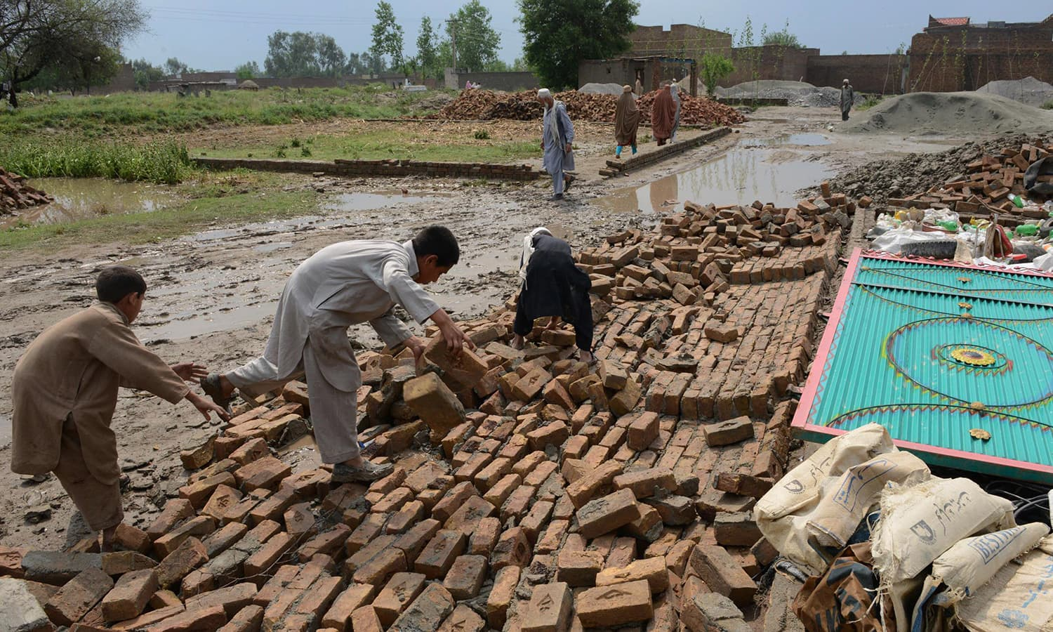 Residents collect bricks after their house collapsed following heavy rain and winds in Peshawar on April 27, 2015. — AFP
