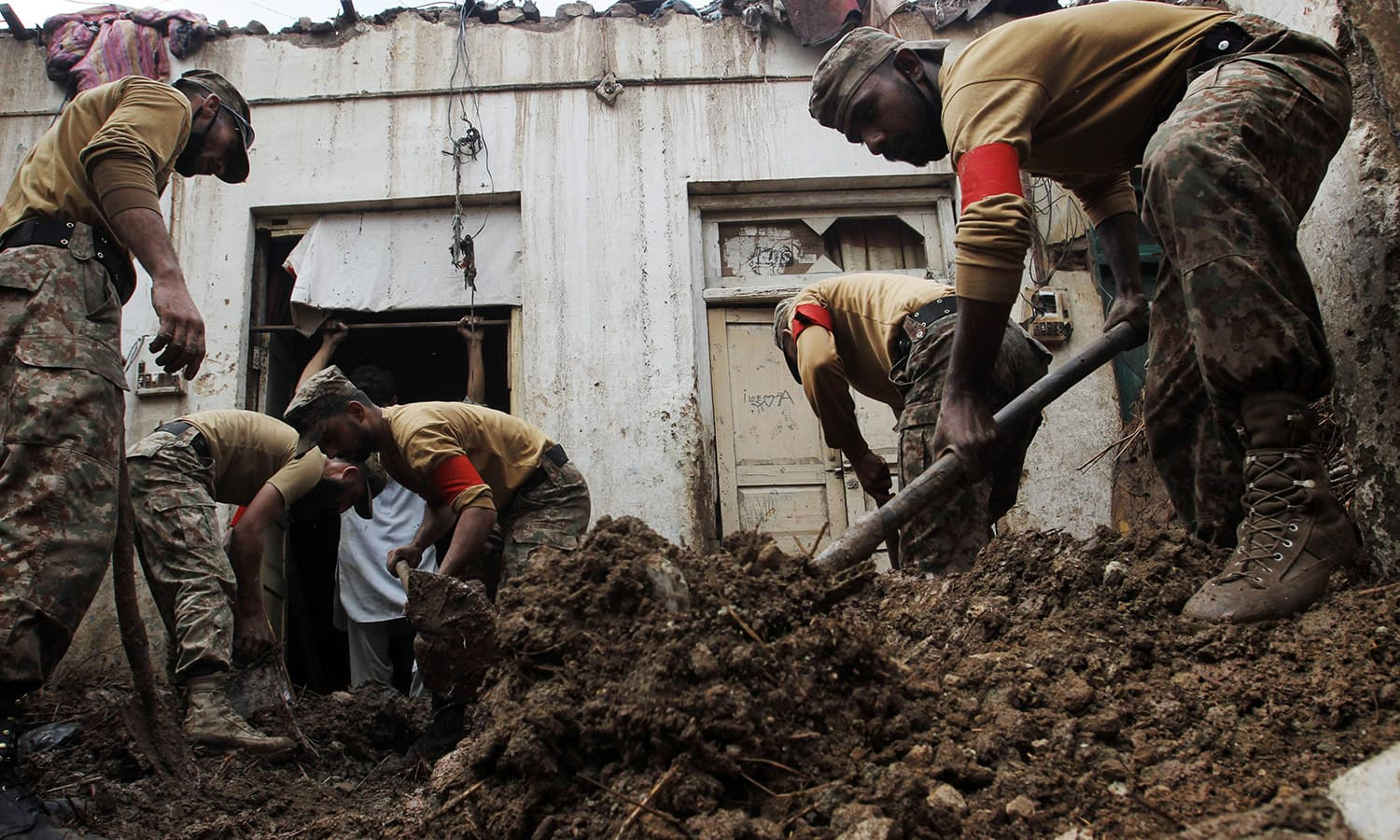 Soldiers remove mud from a home after it was damaged in heavy rain and winds in Peshawar on April 27, 2015. — AFP