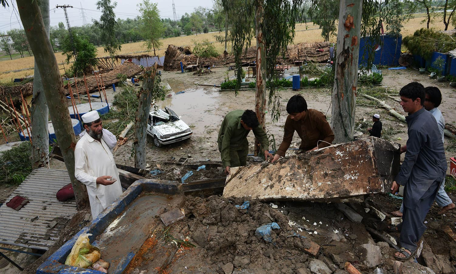 Residents collect belongings at their home after it was damaged in heavy rain and winds in Peshawar. — AFP