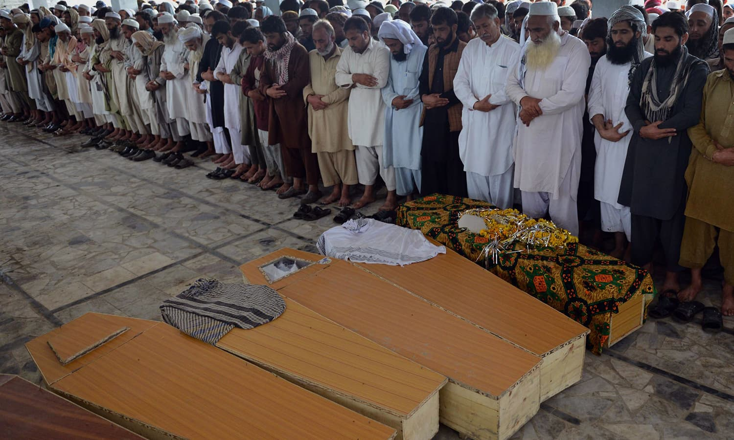 Residents pray alongside the coffins of victims killed in heavy rain and winds in Peshawar on April 27, 2015. — AFP