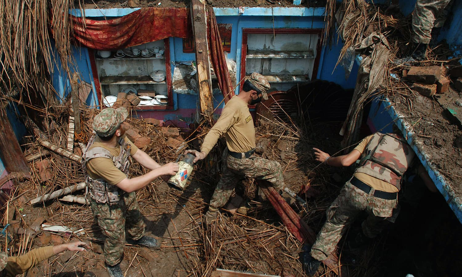 Soldiers remove belongings from a home after it was damaged in heavy rain and winds in Peshawar. — AFP