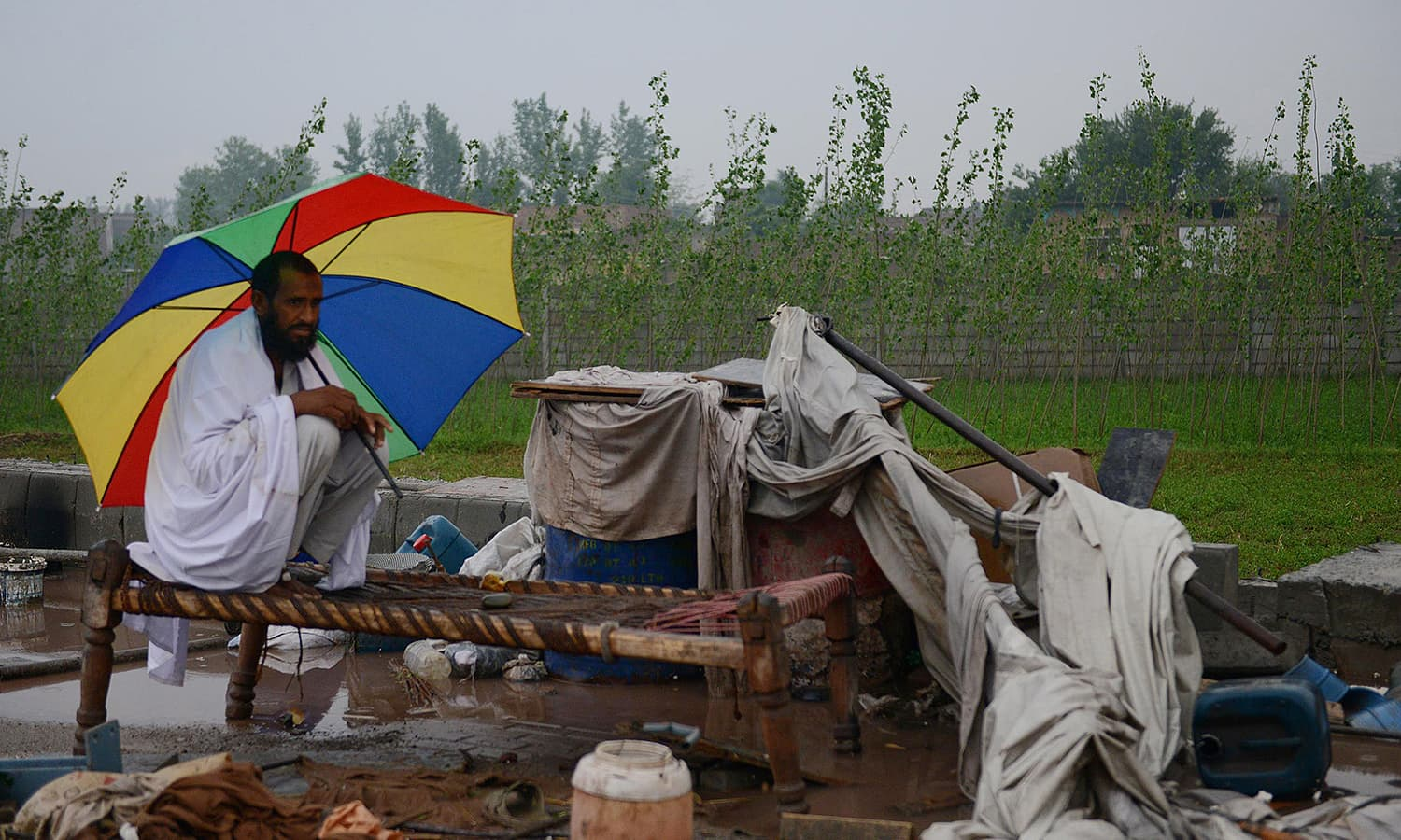 A resident sits alongside with his belongings following heavy rain and winds in Peshawar. — AFP