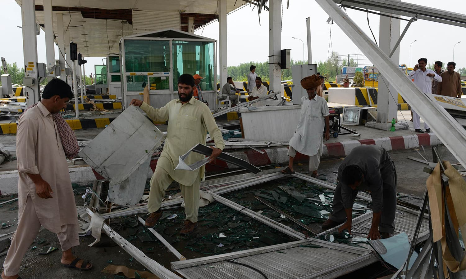 Workers remove debris at a toll booth on a highway after it was damaged in heavy rain and winds in Peshawar. — AFP