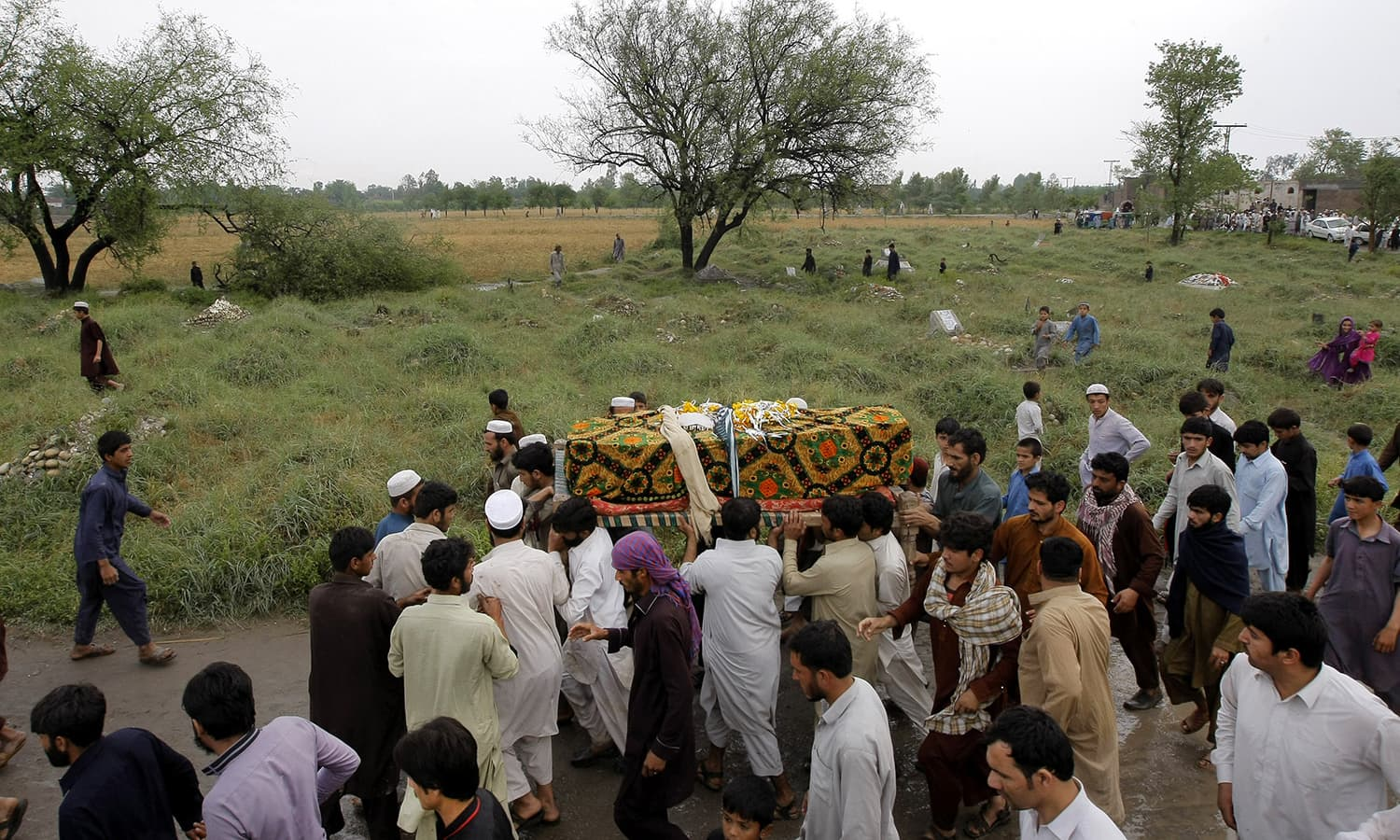 Villagers carry coffins of victims killed from heavy rain and windstorm that reached up to a speed of 120 kph (75 mph) Sunday evening which collapsed hundreds of buildings, uprooted trees, and electric poles, in Peshawar. — AP