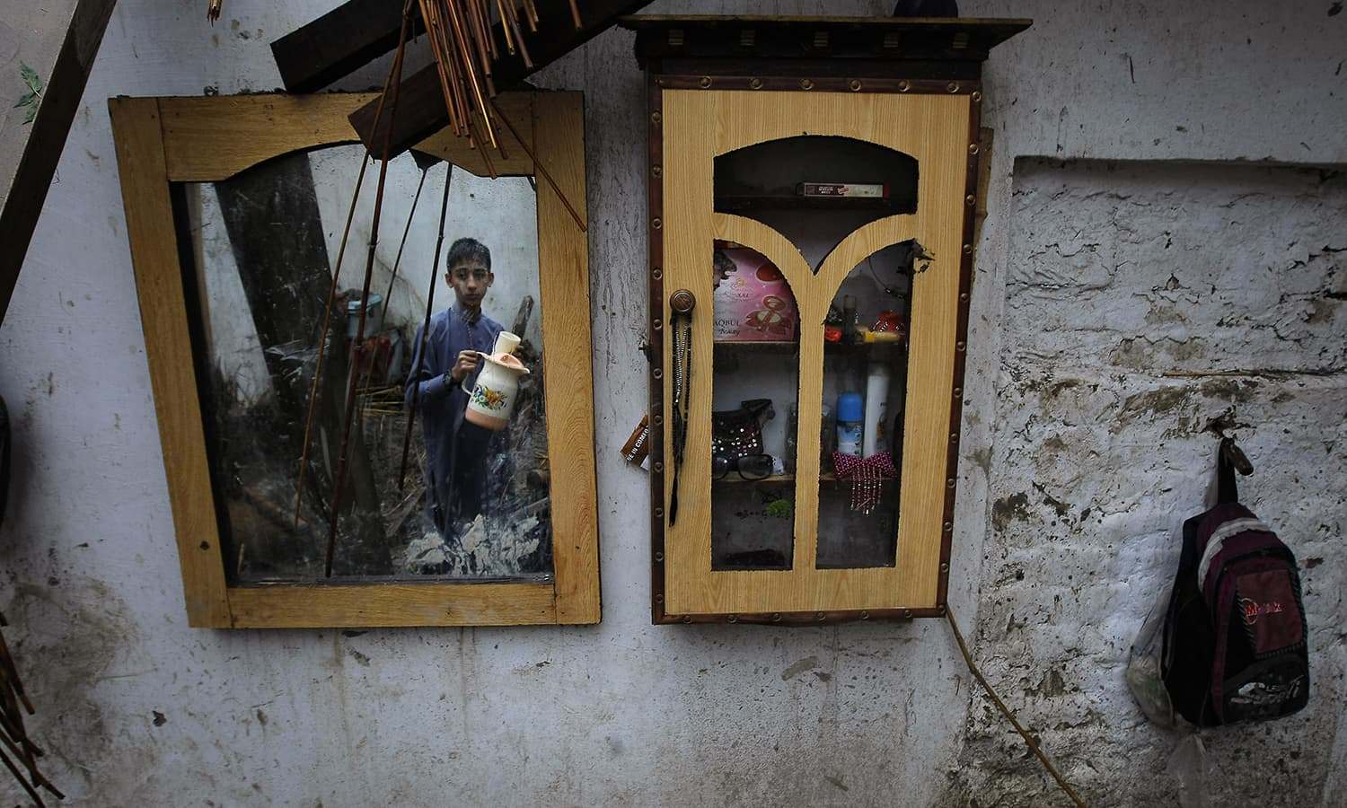 A boy collects his belongings from his home. — AP