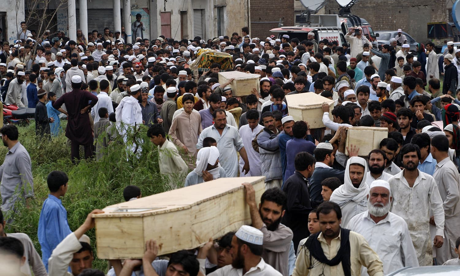 Villagers carry coffins of victims killed from heavy rain and windstorm. — AP