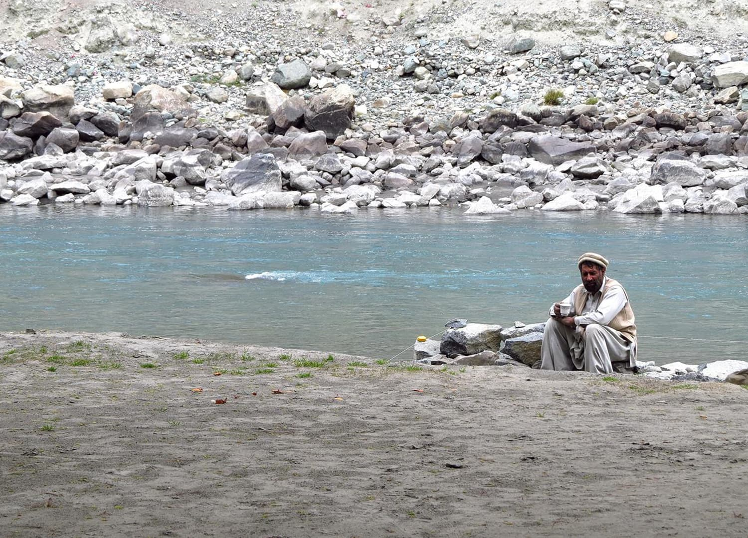 A man sitting next to Gilgit River.