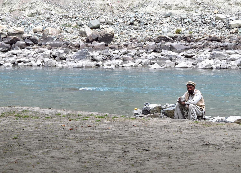 A man sitting next to Gilgit River.