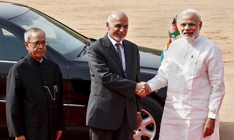 Afghanistan's President Ashraf Ghani shakes hands with India's Prime Minister Narendra Modi as his Indian counterpart Pranab Mukherjee looks on. ─ Reuters