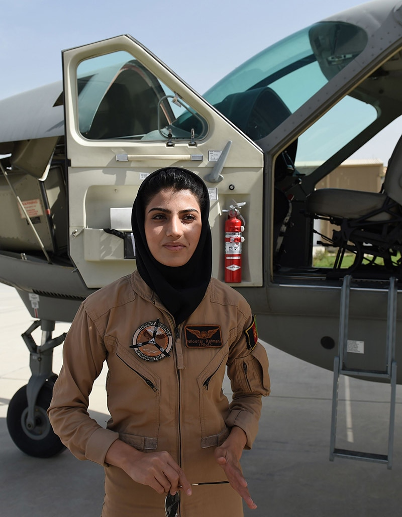 In a picture taken on April 26, 2015, Afghanistan's first female pilot Niloofar Rahmani, 23, poses for a photograph alongside a fixed-wing Afghan Air Force aviator aircraft in Kabul.— AFP