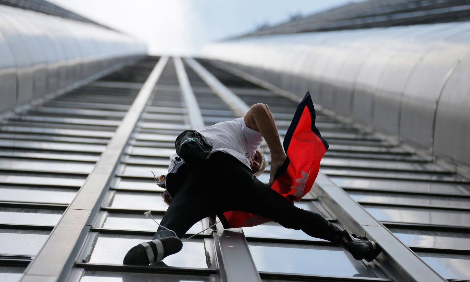"""French climber Alain Robert, also known as """"Spiderman"""", holds the flag of Nepal. – Reuters"""