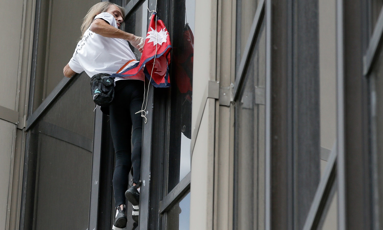 French Spiderman, sets up a Nepal flag as he climbs the Montparnasse tower Paris, France. – AP