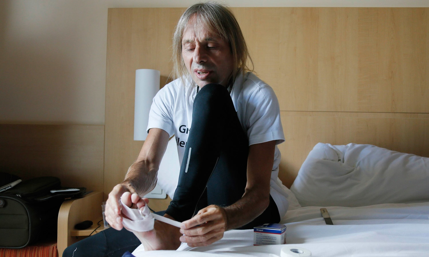 """French climber Alain Robert, also known as """"Spiderman"""", tapes his feet as he prepares to scale the Tour Montparnasse, a 210-metre (689 ft) building in central Paris. – Reuters"""