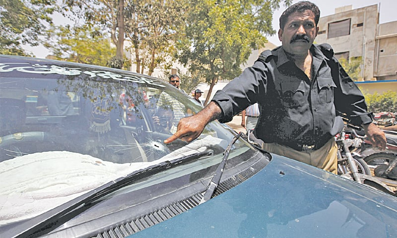 A policeman shows the bullet hole on the slain KU assistant professor's car windscreen on Wednesday.—Reuters