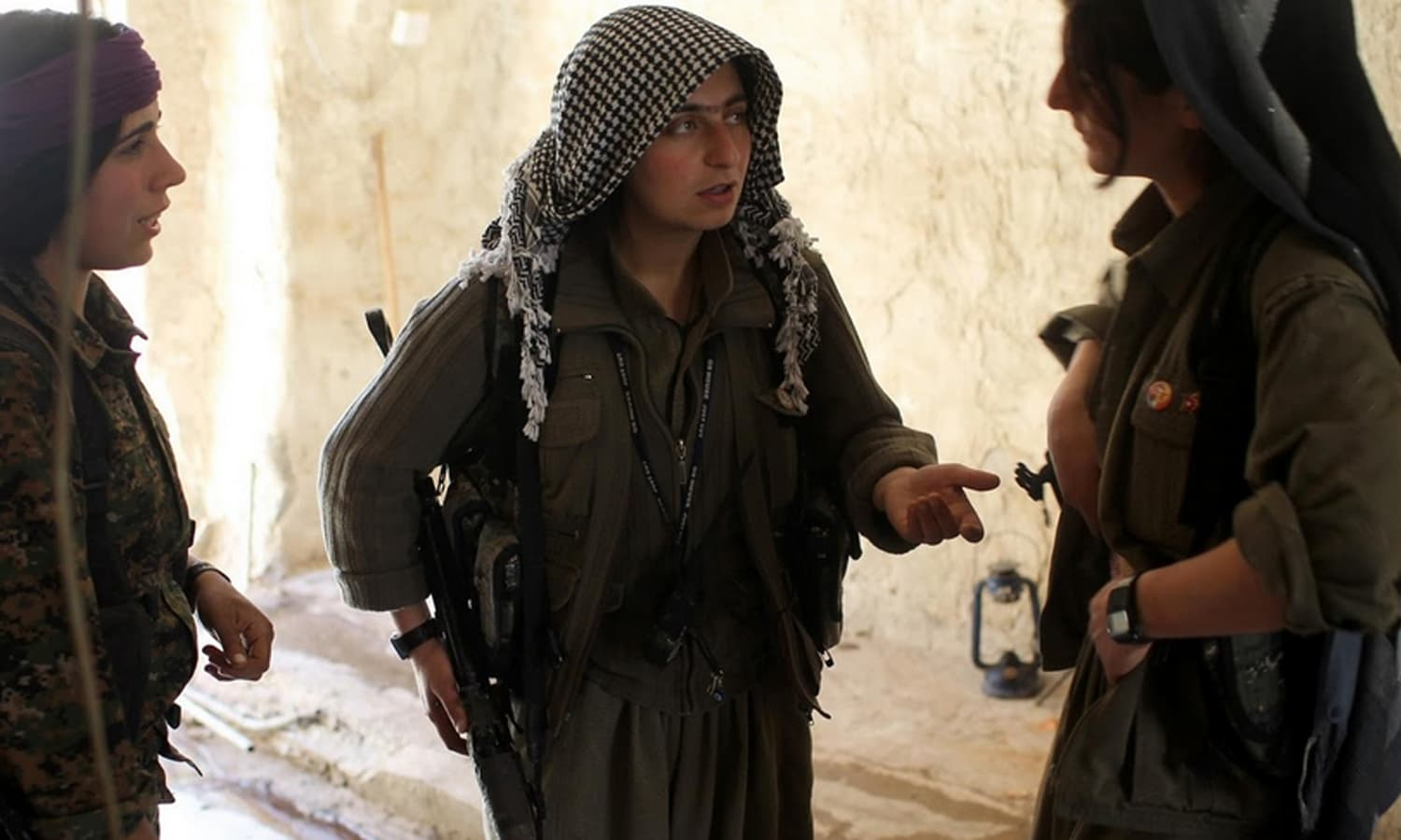 Female PKK fighters discuss how to reach a position that had been hit by Islamic State car bombs in Sinjar.