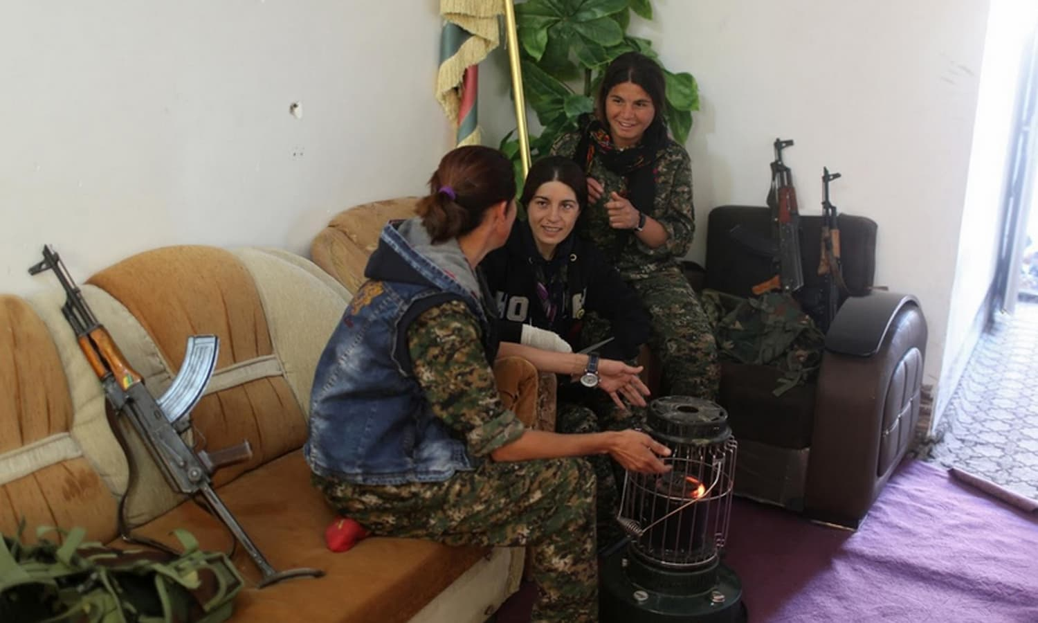 Female fighters talk as they sit around a heater.