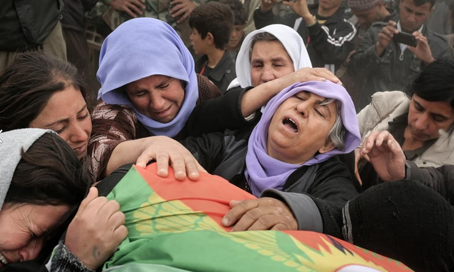 The mother of a Yazidi fighter killed during fighting with Islamic State militants mourns with relatives over his body during a funeral ceremony at a cemetery in Sinjar.