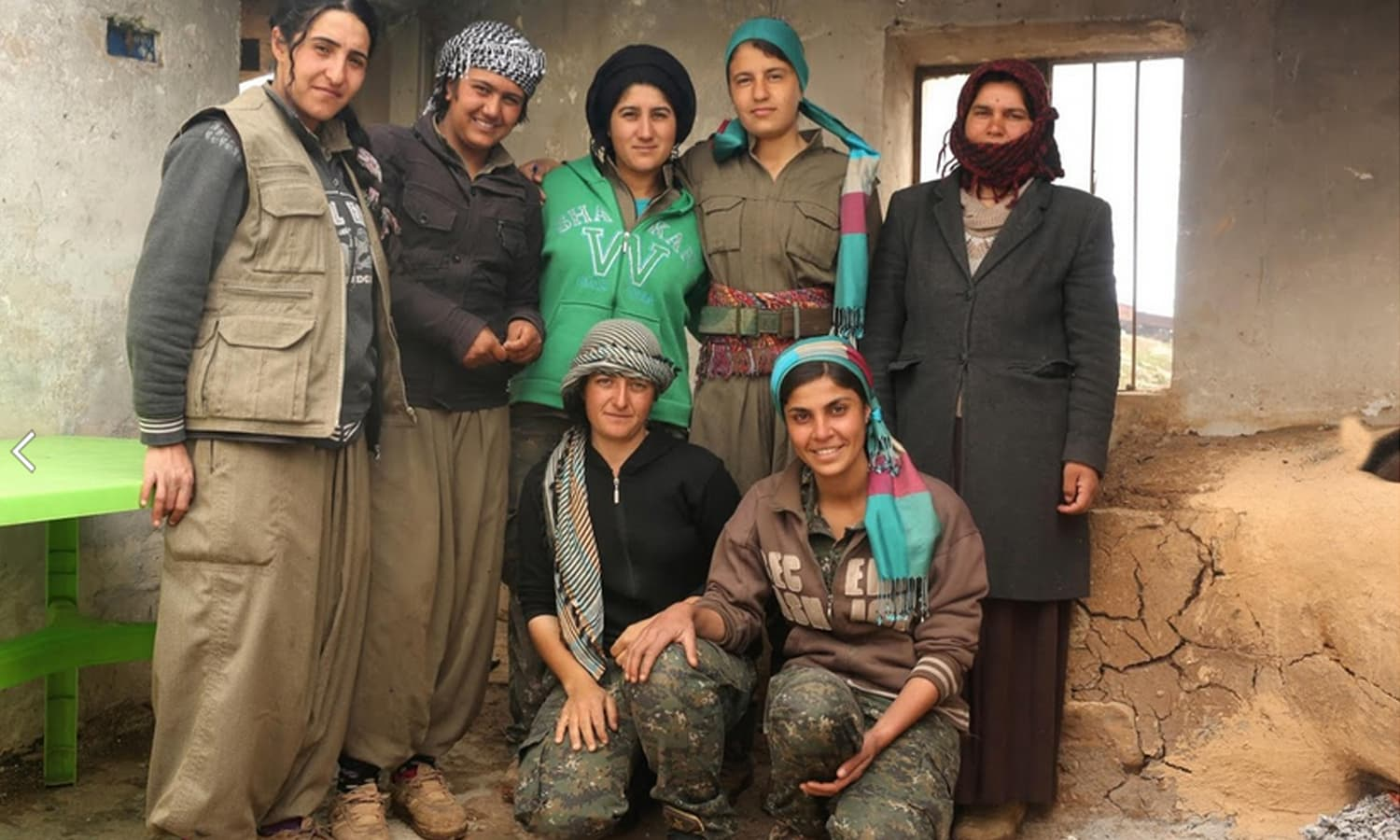 Female Kurdistan Workers Party fighters pose for a picture with a displaced Yazidi woman (R) who lives near the base in Sinjar.