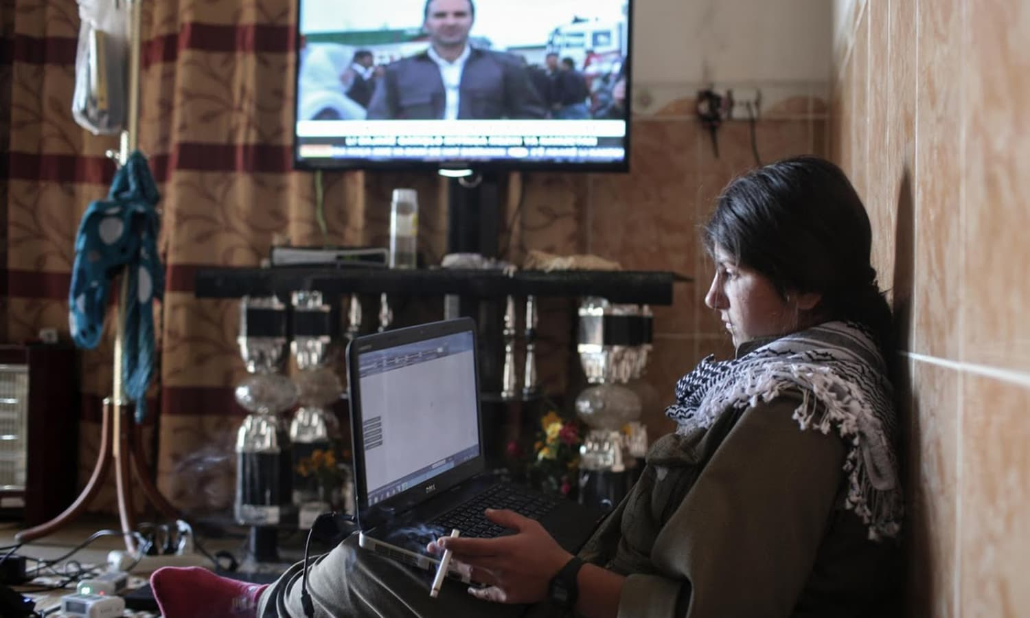 A female PKK fighter works on her laptop while watching a Kurdish TV station at a base in the Sinjar mountains.