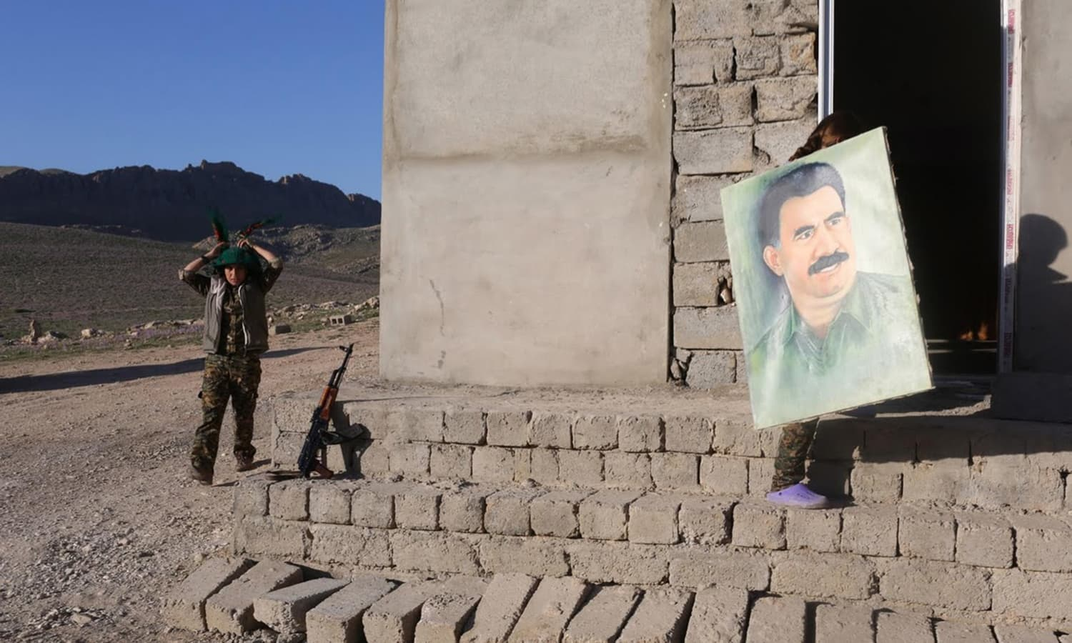 A fighter adjusts her scarf while another carries a picture of jailed Kurdish militant leader Abdullah Ocalan.