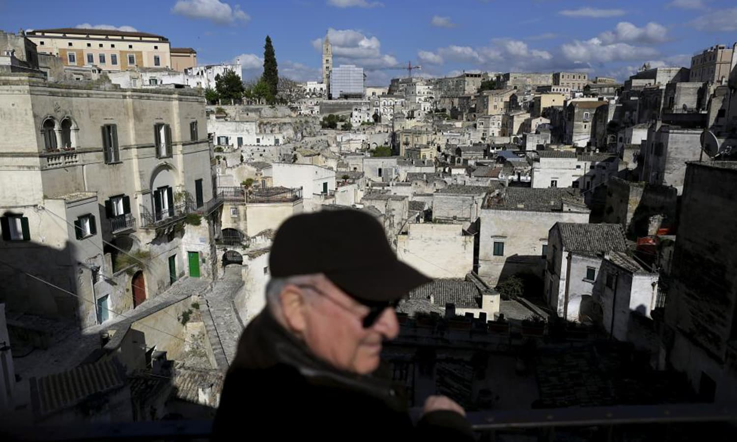 A man stands at a viewpoint from where he can see Matera's Sassi, southern Italy.