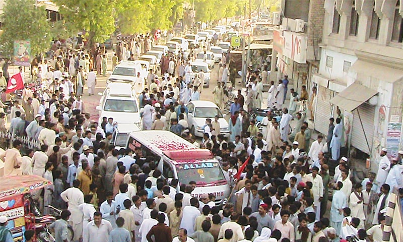 THE ambulance carrying the coffin of JSQM-A leader Abdul Wahid Arisar in a convoy of vehicles to the Vauri village graveyard in Umerkot on Sunday.—Dawn