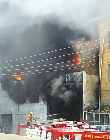 Fire tenders look small in front of the huge fire that broke out and spread from a polyester yarn warehouse in the SITE area on Monday.—PPI