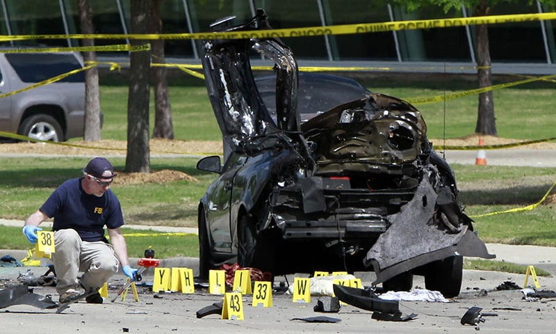 Members of the FBI Evidence Response Team investigate the crime scene outside of the Curtis Culwell Center in Texas. ─ AFP