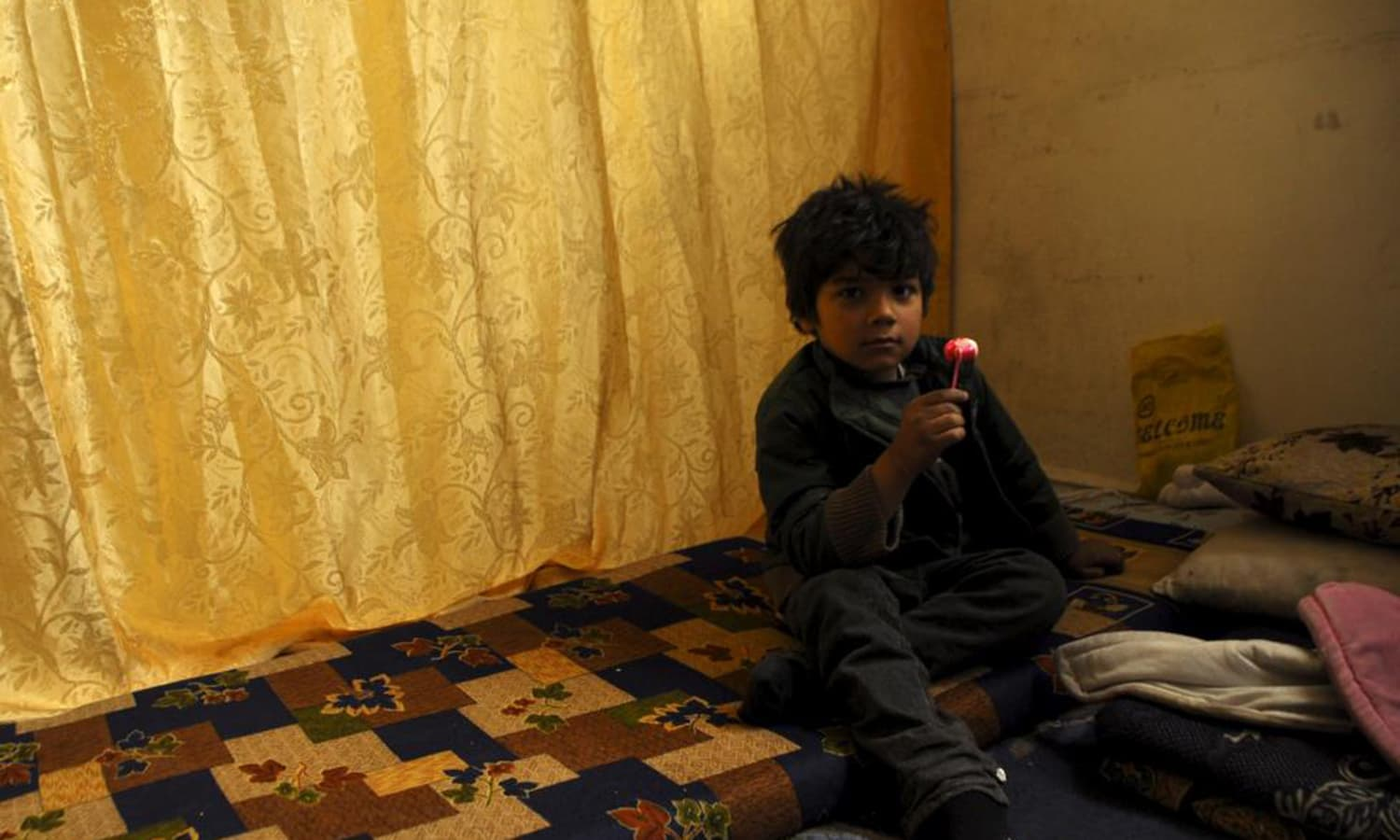 A boy that fled Yarmouk camp, now living inside an abandoned school where they sought refuge, sits inside a makeshift classroom in the rebel held town of Yalda, south Damascus. — Reuters