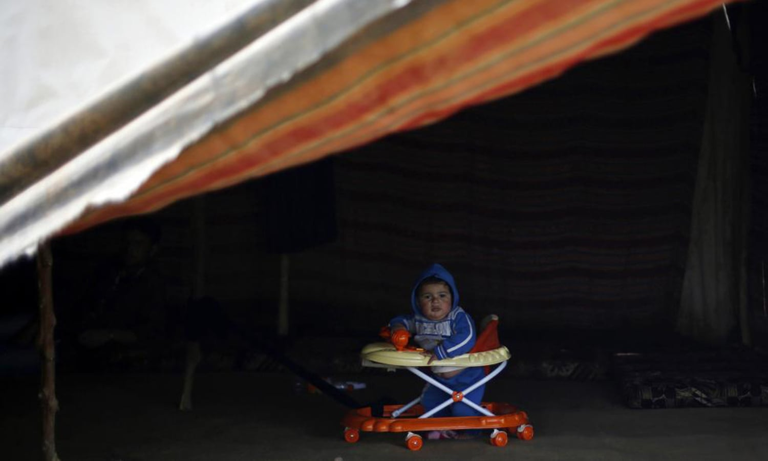 A Syrian refugee boy from Idlib, who now lives in Jordan after his family fled the violence in Syria, sits in a baby walker in his family's tent at a tented settlement in Madaba city, near Amman. — Reuters