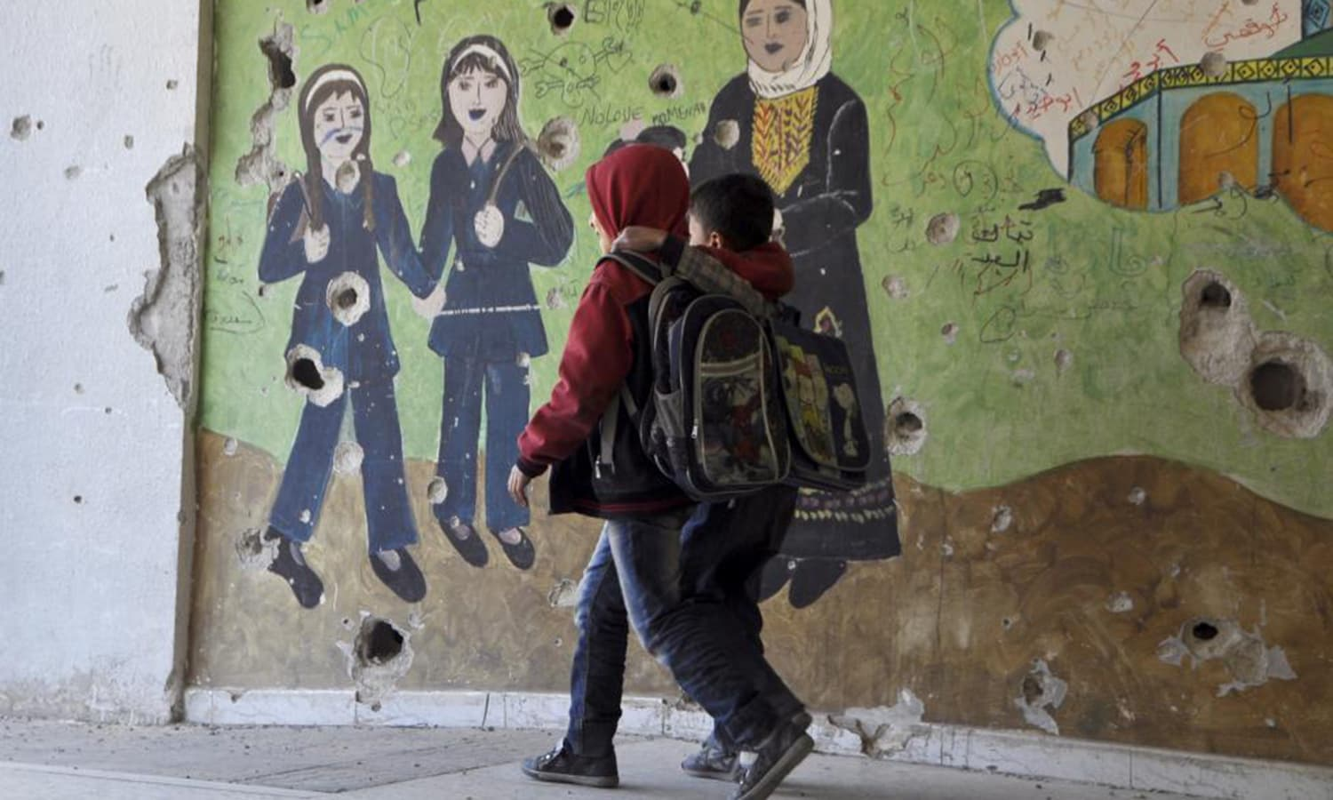 """Children walk beside a painted wall inside Jarmaq school in Yarmouk camp, April 14, 2015. The text on the wall reads in Arabic """"It's my right to learn."""" — Reuters"""