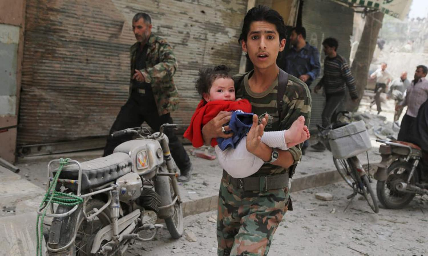 A man carries a child at a site hit by what activists say was a barrel bomb dropped by forces loyal to Syria's President Bashar al-Assad, in al-Kalaseh neighborhood in Aleppo. — Reuters