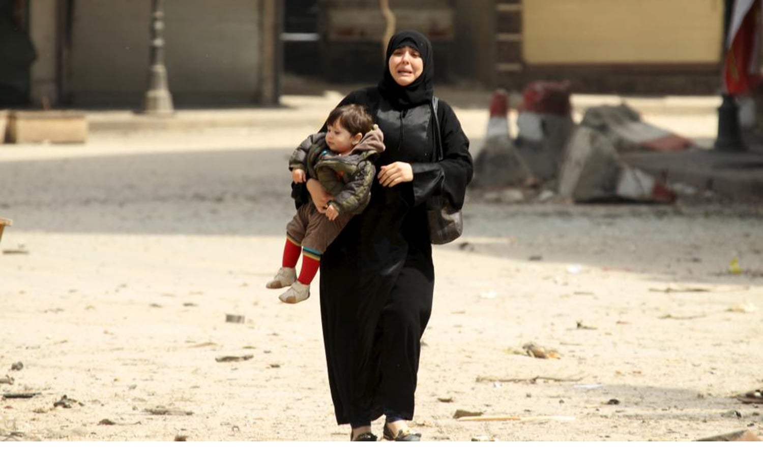 A woman carrying a child reacts at a damaged site after what activists said was shelling by forces loyal to Syria's president Bashar al-Assad on a mosque in Idlib city. — Reuters