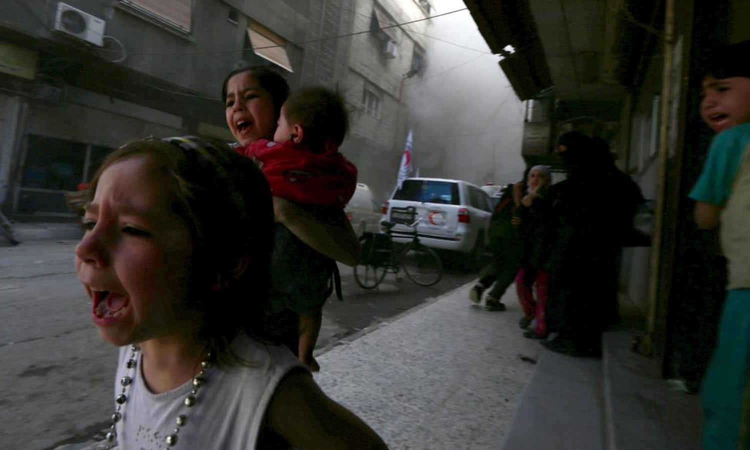 Children react after what activists said was shelling by forces loyal to Syria's President Bashar al-Assad near the Syrian Arab Red Crescent center in the Douma neighborhood of Damascus. — Reuters