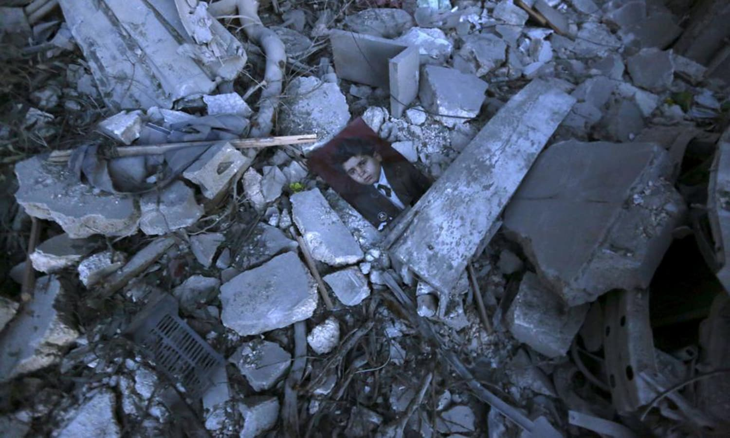 A picture lies amidst debris of collapsed buildings after what activists said was a barrel bomb dropped by forces loyal to Syria's President Bashar al-Assad in the Al-Qatrgi neighbourhood of Aleppo.— Reuters