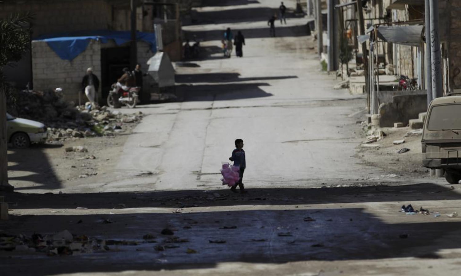 A boy carries bags of cotton candy for sale as he stands along a street in Maaret al-Naaman town in Idlib province. — Reuters