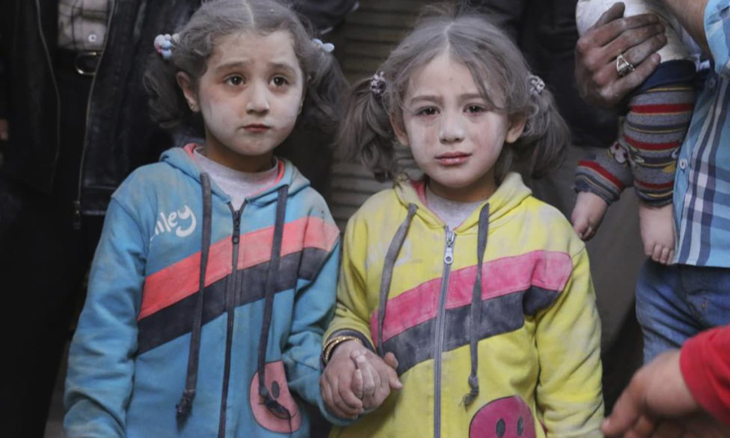 Girls who survived what activists said was a ground-to-ground missile attack by forces of Syria's President Bashar al-Assad, hold hands at Aleppo's Bab al-Hadeed district. — Reuters