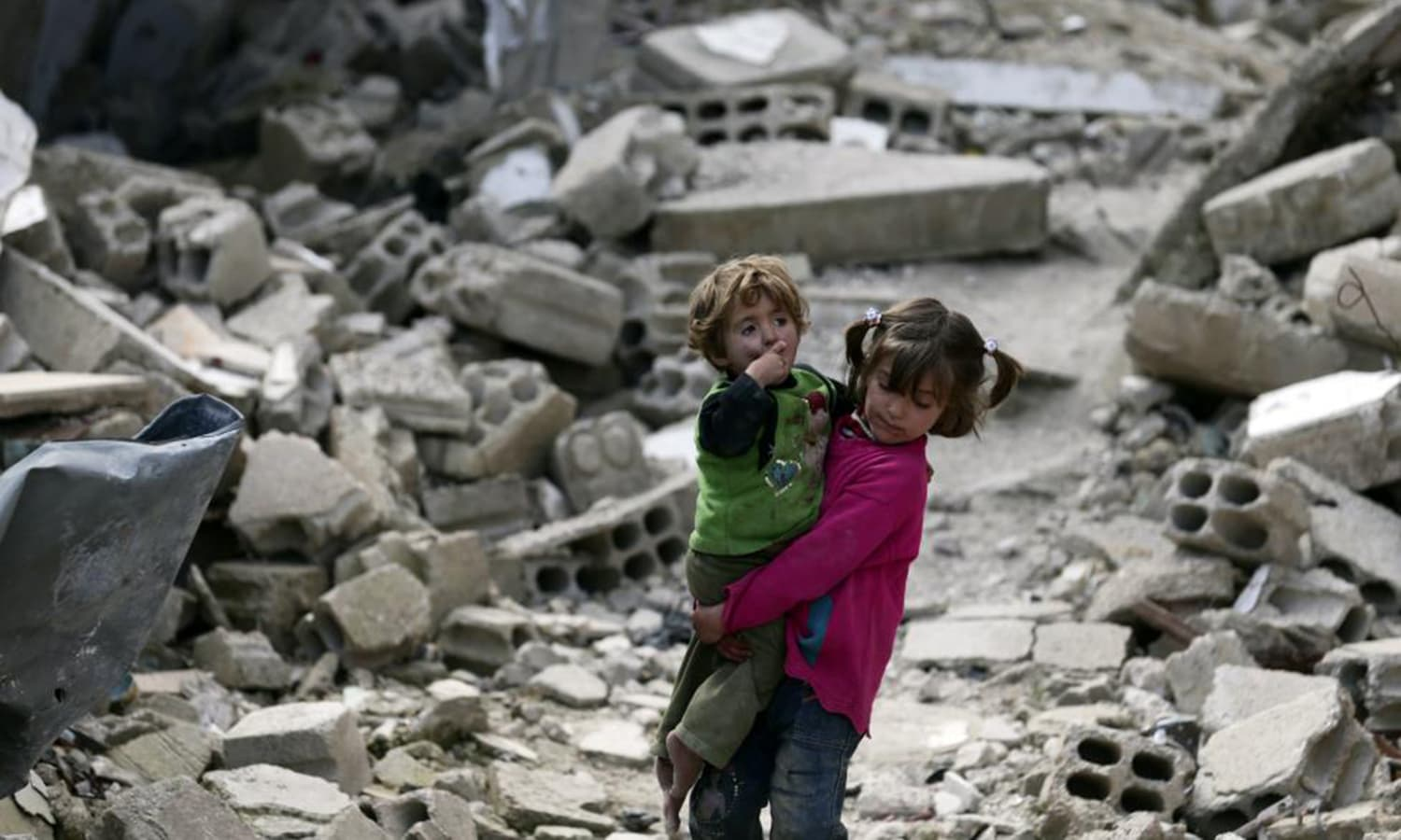 Local resident Israa holds her sister Boutol as they make their way through rubble of damaged buildings in the Douma neighborhood of Damascus. — Reuters
