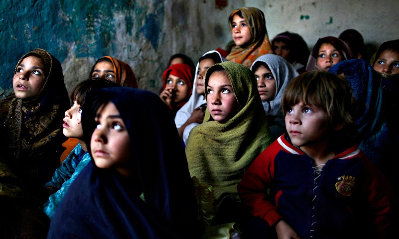Pakistani schoolgirls, who were displaced with their families from tribal areas due to fighting between militants and the army, listen to their teacher in a poor neighborhood on the outskirts of Islamabad.