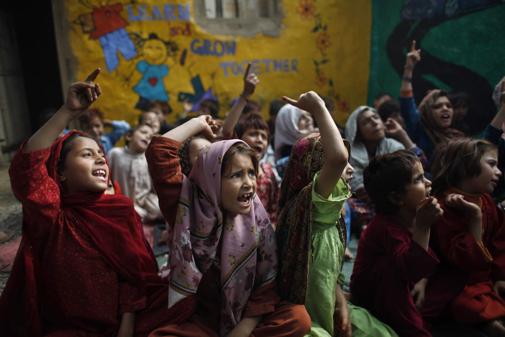 Pakistani schoolgirls, who were displaced with their families from tribal areas due to fighting between militants and the army, listen to their teacher in a poor neighborhood on the outskirts of Islamabad. -AP
