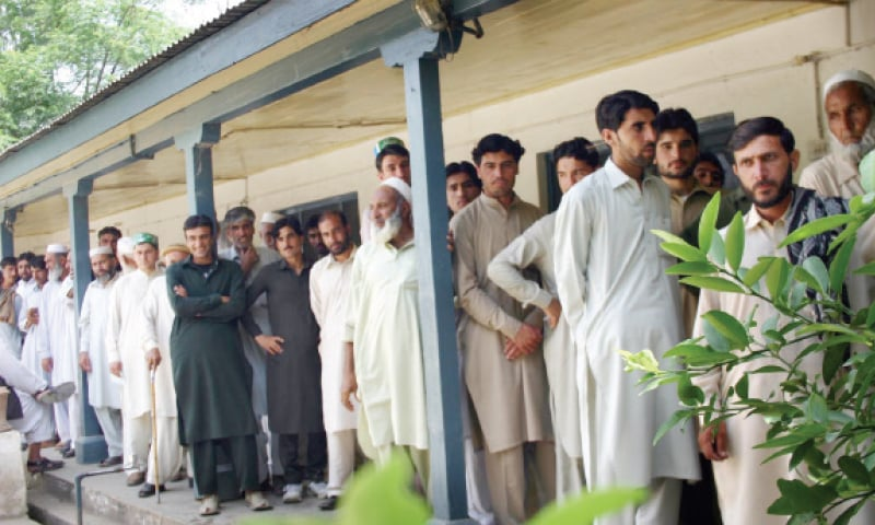Voters line up outside a polling station in Lower Dir on Thursday. — INP