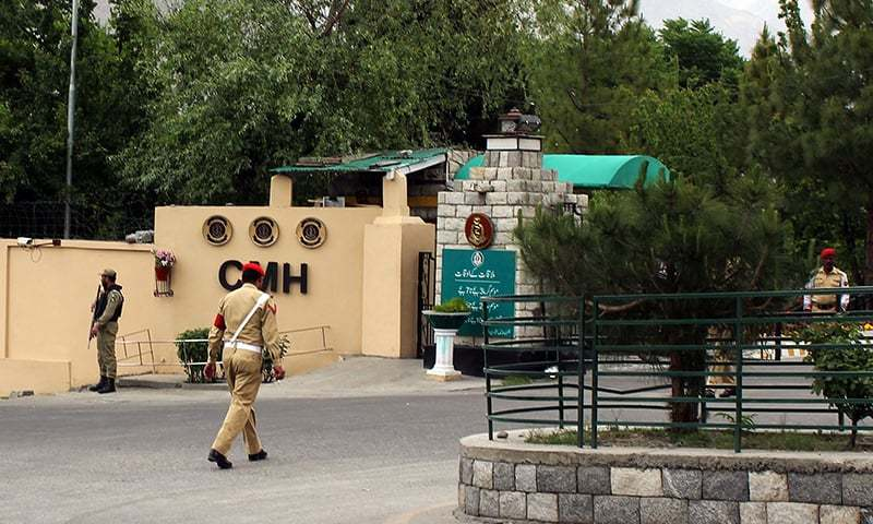 Soldiers stand guard outside the Combined Military Hospital where victims of a helicopter crash were brought for treatment in Gilgit on May 8, 2015. — AFP