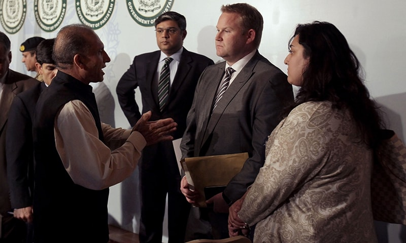 Foreign Secretary Aizaz Chaudhry expresses his condolences to a Norwegian diplomat after a press conference on the helicopter crash that killed a number of foreign dignitaries. -AP