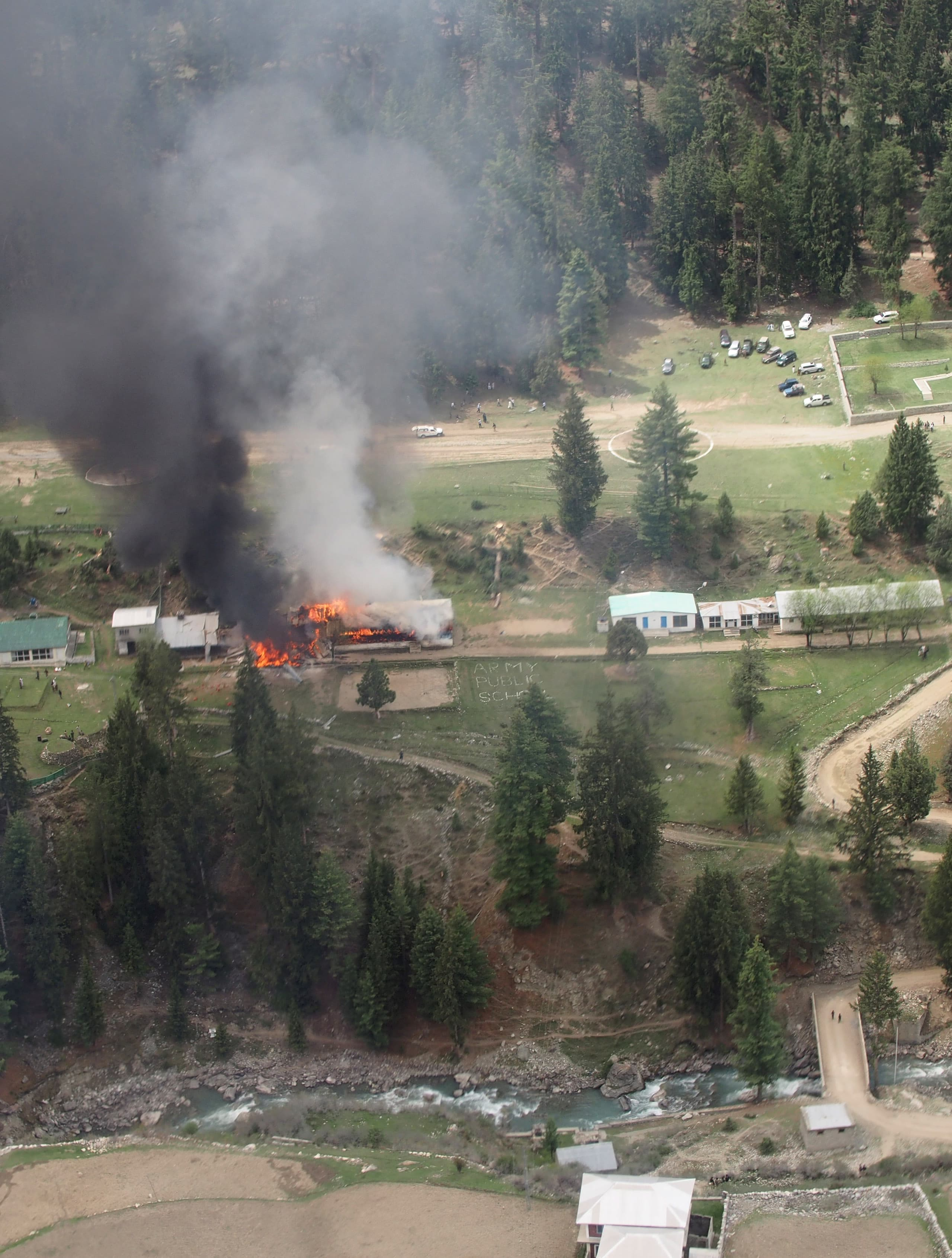 Flame and smoke rises from the site where a military helicopter crashed in  Gilgit. - AP