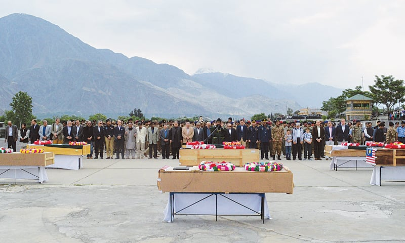 GILGIT: Officials and foreign diplomats pay their respects to the victims of the army helicopter crash on Saturday.—AFP