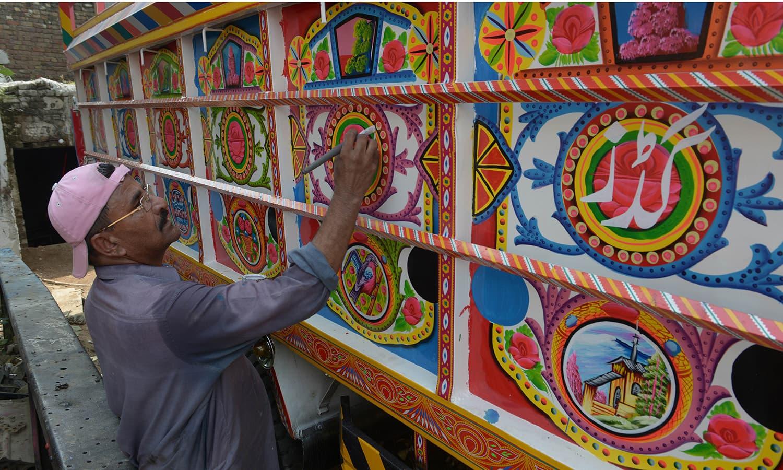 A painter decorates a truck in Rawalpindi.