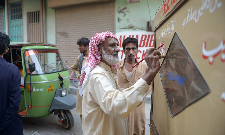 Painter Haji Habib ur Rehman writes poetry on a rickshaw outside his shop in Rawalpindi.